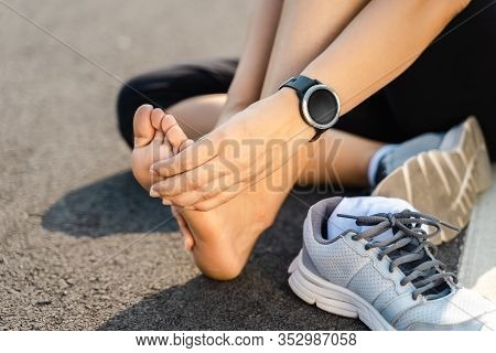 Running Injury Leg Accident- Sport Woman Runner Hurting Holding Painful Sprained Ankle In Pain. Fema