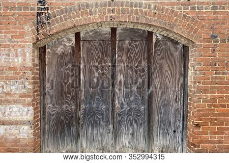 An Old Coal Chute Door Behind Old Red Brick House