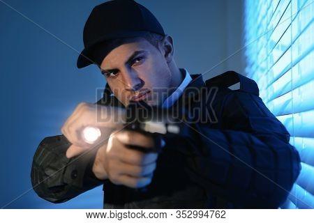 Professional Security Guard With Flashlight And Gun Near Window In Dark Room