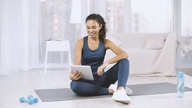 Lovely Hispanic Woman With Tablet Computer Watching Workout Video On Yoga Mat At Home