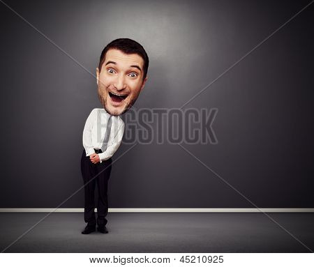 full-length picture of funny businessman with big head over dark background