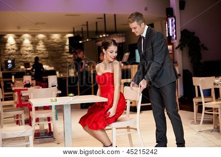 Young man helping  his girlfriend to accommodate on chair