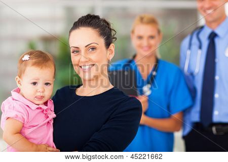portrait of happy mother holding her baby girl in doctors office