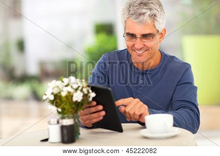 smiling middle ged man surfing the internet using tablet computer at home