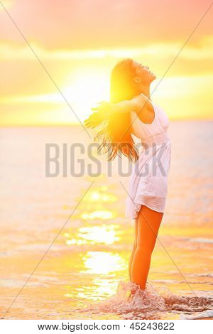 Free woman enjoying freedom feeling happy at beach at sunset. Beautiful serene relaxing woman in pure happiness and elated enjoyment with arms raised outstretched up. Asian Caucasian female model. poster