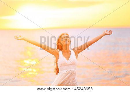 Liberdade mulher felizes e livre braços abertos na praia ao pôr do sol ensolarado. Bela mulher feliz alegre looki