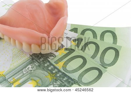 denture and euro bills, symbolic photo for dentures, treatment costs and payment