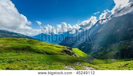 Peaceful alpine meadow mountain panorama in Himalayas with sun rays poster