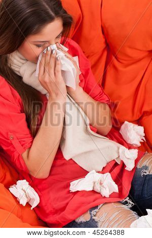 Young woman sitting at home with cold and rheum
