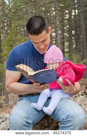 Baby girl sitting on dad???s lap reading KJV Bible (King James Version) poster