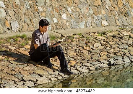 Young man sitting by a lake reading the Bible poster