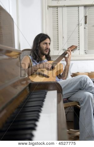 Man Playing Guitar By Piano - Vertical