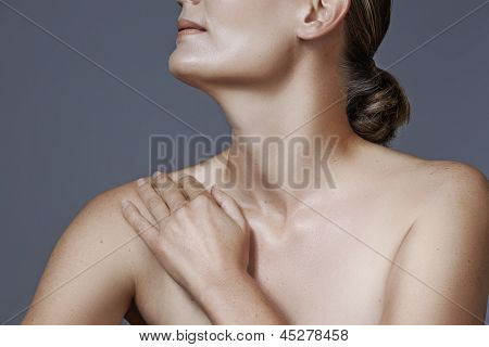Portrait of 40 year old woman with beautiful skin and natural makeup on studio background