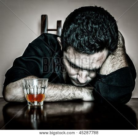 Alcoholism : Grunge bleached portrait of a lonely and desperate drunk hispanic man
