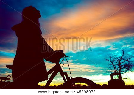 Girl with a bicycle watching the sunset poster