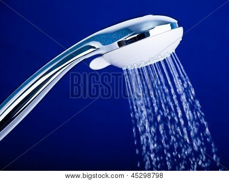 Shower head with running water against blue background