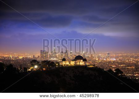 Los Angels city skyline at night with Griffith Observatory in foreground and downtown in background. poster