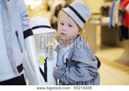 Cute little boy poses near two mannequins in children clothing shop.