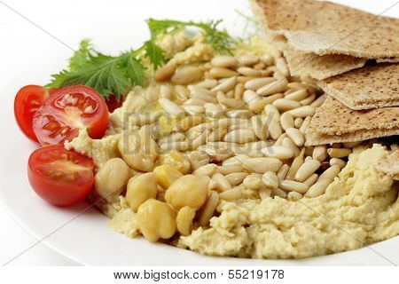 Lebanese hummus with pine-nuts on a plate with some flat bread, sliced cherry tomatoes and a garnish of young salad leaves, topped off with a drizzle of olive oil