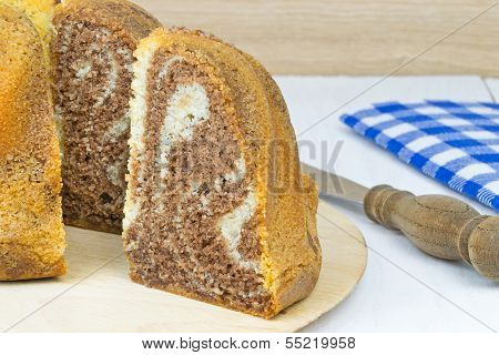 A marble sponge cake and slice on wooden table poster