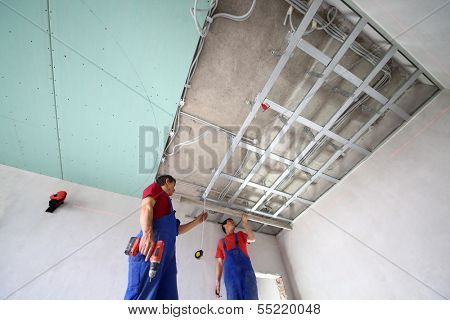 The two workers set the ceiling profile in the new flat