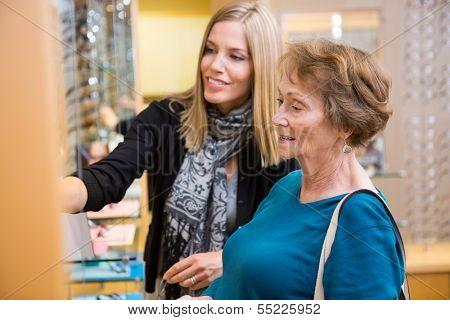 Salesgirl assisting senior female customer in selecting glasses at store