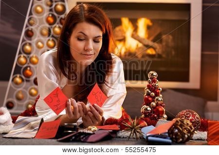 Smiling girl thinking to decide on christmas presents, arranging name tag with tie, lying in cosy living room in front of fireplace.