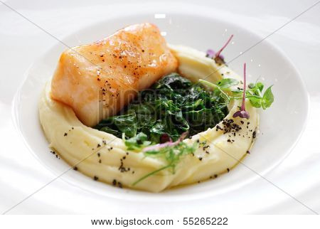 Fried black cod fillet with potato mash and spinach close-up