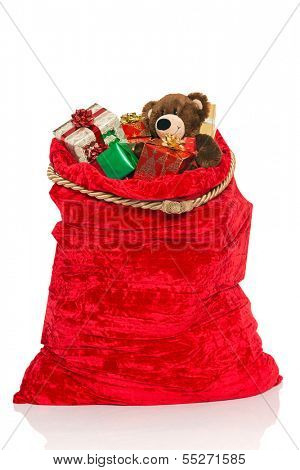 A red Christmas sack full of gift wrapped presents and a handmade bear, isolated on a white background.