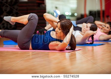 Beautiful young women doing crunches during a class at a gym poster