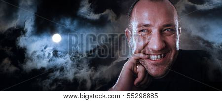 Dramatic portrait of adult man with sly facial expression, biting his fingernail