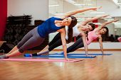 Group of three young women practicing the side plank pose during yoga class in a gym poster