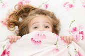 Little girl having childhood nightmares and fears hiding under the quilt poster