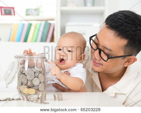 Asian family lifestyle at home. Father and child saving coins to money jar, financial planning concept.