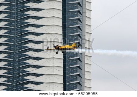 PUTRAJAYA, MALAYSIA - MAY 17, 2014: Nigel Lamb of Great Britain, in a MXS-R plane flies past the skyscrapers of Putrajaya at the qualifying session of the Red Bull Air Race World Championship 2014.