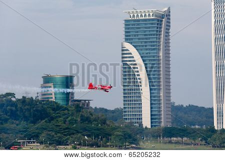 PUTRAJAYA, MALAYSIA - MAY 17, 2014: Pete Mcleod from Canada in an Edge 540 V3 plane flies through the race course over Putrajaya lake at the Red Bull Air Race World Championship 2014.