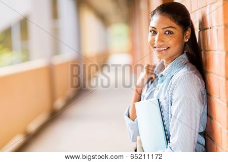 happy indian college student leaning against wall