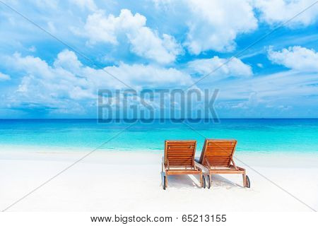Two empty sunbed on the beach, beautiful seascape, relaxation on Maldives island, luxury summer vacation concept