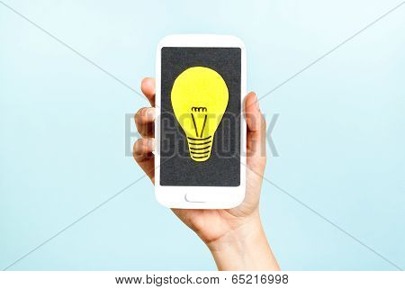 Yellow light bulb on black screen paper phone. Ideas,insight,clever,crowdfunding concept.