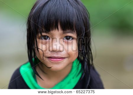 BANAUE, PHILIPPINES, DECEMBER 04 : A young unidentified Filipino little girl is posing under the rain in the village of Banaue, north Luzon, Philippines, on december 04, 2013