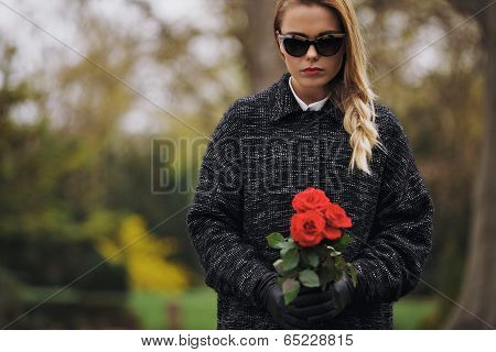 Young Woman At Graveyard With Fresh Roses