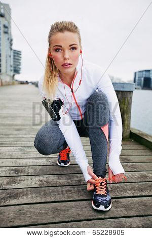 Female Athlete Tying Her Laces Before A Run