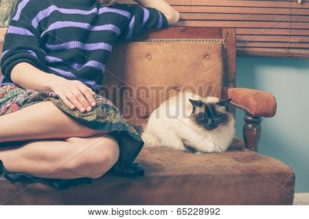 A young woman is sitting on a sofa with her cat poster