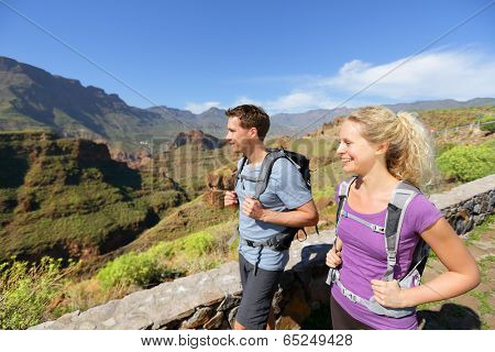 Hiker couple hiking on Gran Canaria. Romantic hikers enjoying hike in beautiful mountain forest landscape. Blonde woman hiker and Caucasian man on Gran Canaria, Canary Islands, Spain.