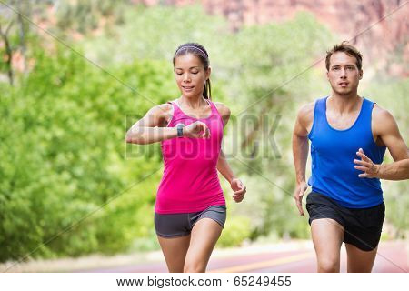 Runners - mixed multicultural couple training outside in nature. Fitness asian young smiling model checking time or pulse on heart rate monitor watch and male model jogging. poster