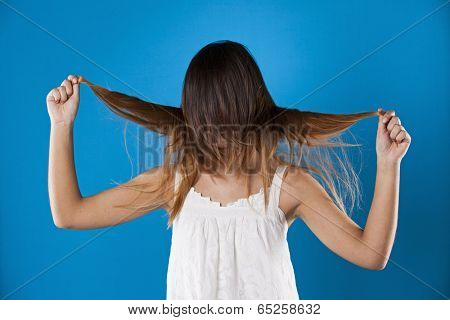 Woman with hair over her face in a blue background