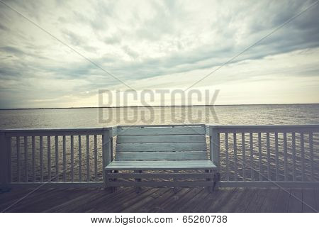 Empty bench along the boardwalk overlooking the Currituck sound in Duck in the Outer Banks of North Carolina