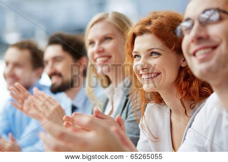 Photo of happy business people applauding at conference, focus on smiling female poster