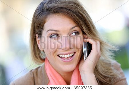 Portrait of blond woman using smartphone poster