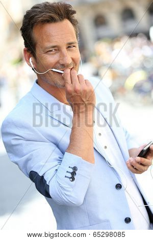 Trendy handsome man talking on phone with handsfree
